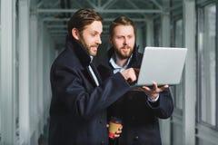 Deux hommes d'affaires beaux travaillant ensemble sur un projet au lobby photos stock