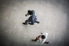Deux hommes d'affaires courant la construction d'affaires de cuvette Course d'hommes d'affaires Image libre de droits