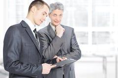 Deux hommes d'affaires dans la discussion en étudiant les documents importants Photo stock