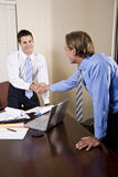 Deux hommes d'affaires dans le bureau se serrant la main Images stock