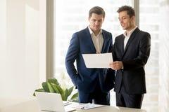 Deux hommes d'affaires de sourire parlant de l'investissement éligible, discu Photographie stock libre de droits