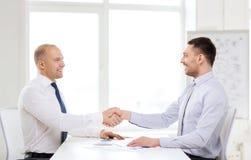 Deux hommes d'affaires de sourire se serrant la main dans le bureau Photo stock