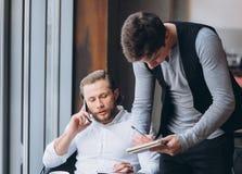 Deux hommes d'affaires discutant le travail et à l'aide du comprimé Images libres de droits