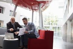 Deux hommes d'affaires discutent le document dans le lobby du bureau moderne Photos stock