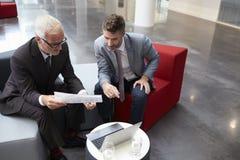 Deux hommes d'affaires discutent le document dans le lobby du bureau moderne Image libre de droits