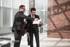 Deux hommes d'affaires discutent le document se tenant dans le lobby de bureau Photos libres de droits