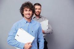 Deux hommes d'affaires gais tenant des dossiers Photographie stock libre de droits