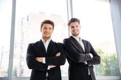Deux hommes d'affaires heureux se tenant avec des bras ont croisé dans le bureau Images stock