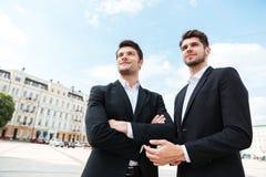 Deux hommes d'affaires heureux se tenant dehors Photographie stock