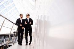 Deux hommes d'affaires marchant le long dans le bureau moderne Image stock