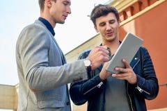 Deux hommes d'affaires modernes utilisant la Tablette de Digital dehors Photo stock