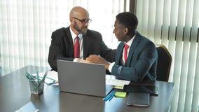 Deux hommes d'affaires multiraciaux se serrent la main en l'honneur d'une affaire dans le bureau dans le mouvement lent clips vidéos