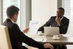 Deux hommes d'affaires multiraciaux sur la réunion discutant le repo financier Photos stock