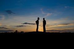 Deux hommes d'affaires négocient des affaires dans le coucher du soleil Image libre de droits