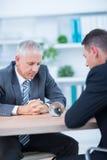 Deux hommes d'affaires observant la boule de cristal Image libre de droits