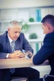 Deux hommes d'affaires observant la boule de cristal photos stock