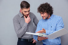 Deux hommes d'affaires occasionnels lisant des documents dans le dossier Photo stock