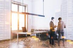 Deux hommes d'affaires parlant dans un bureau blanc Image stock