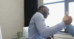 Deux hommes d'affaires parlant le support devant la fenêtre dans le bureau coworking moderne tandis que gens d'affaires banque de vidéos