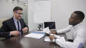 Deux hommes d'affaires parlant tout en se reposant à la table dans le bureau moderne clips vidéos