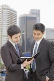 Deux hommes d'affaires regardant le bloc-notes Images libres de droits