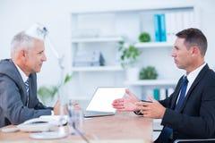 Deux hommes d'affaires sérieux parlant et travaillant photo stock