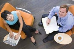 Deux hommes d'affaires s'asseyant à l'intérieur ayant le contact Image stock