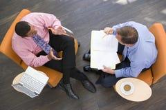Deux hommes d'affaires s'asseyant à l'intérieur ayant un contact Photo libre de droits
