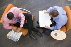 Deux hommes d'affaires s'asseyant à l'intérieur ayant un contact Photos libres de droits