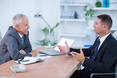 Deux hommes d'affaires s'asseyant et parlant Image libre de droits
