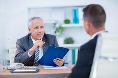 Deux hommes d'affaires s'asseyant et parlant et travaillant Image stock