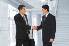 Deux hommes d'affaires saluent en collage de centre d'affaires Images stock