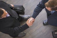 Deux hommes d'affaires se serrant la main à l'intérieur Photo stock