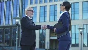 Deux hommes d'affaires se serrant la main accord dehors, de fusion et d'acquisition clips vidéos