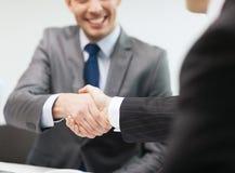 Deux hommes d'affaires se serrant la main dans le bureau Images libres de droits