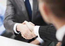 Deux hommes d'affaires se serrant la main dans le bureau Images stock