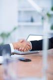 Deux hommes d'affaires se serrant la main et le travail Photo stock