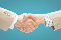 Deux hommes d'affaires se serrant la main - fermez-vous vers le haut du studio tiré sur le fond bleu-clair photos libres de droits