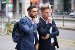 Deux hommes d'affaires se tenant dans la rue et regardant quelque chose Photo stock