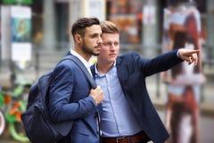 Deux hommes d'affaires se tenant dans la rue et regardant quelque chose Photo libre de droits