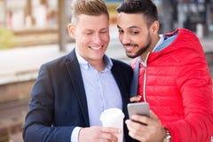 Deux hommes d'affaires se tenant extérieurs et regardant le téléphone Photo libre de droits