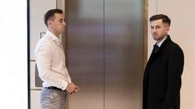 Deux hommes d'affaires se tenant près de l'ascenseur Hommes d'affaires près d'un ascenseur dans le bureau image stock