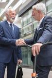 Deux hommes d'affaires supérieurs heureux se serrant la main, se tenant devant un immeuble de bureaux image libre de droits