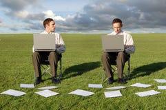 Deux hommes d'affaires sur des ordinateurs portatifs Photographie stock