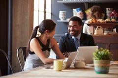 Deux hommes d'affaires travaillant à l'ordinateur portable en café photographie stock