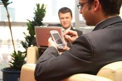 Deux hommes d'affaires travaillant avec l'ordinateur portatif et le palmtop dans l'environnement de bureau. Image stock