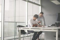 Deux hommes d'affaires travaillant ensemble dans le bureau Document de lecture Images libres de droits