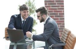 Deux hommes d'affaires travaillant ensemble utilisant l'ordinateur portable sur la réunion d'affaires dans le bureau Photo stock
