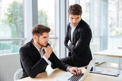 Deux hommes d'affaires travaillant et à l'aide de l'ordinateur portable dans le bureau ensemble images libres de droits