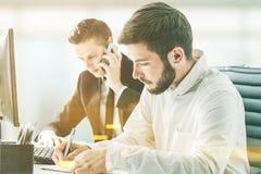 Deux hommes d'affaires travaillant sur leur lieu de travail Images libres de droits